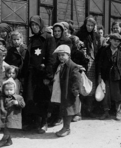 Black and white photo of Jews with Star of David patches sewn on their jackets stand in line near railroad cars during the Holocaust